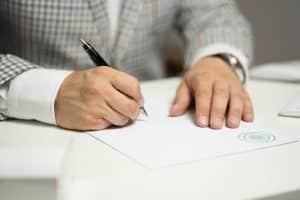 עורך דין ממלא מסמכים עבור תביעה לתשלום דמי פגיעה