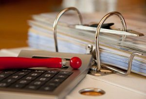 עט אדום על מחשבון על גבי קלסר פתוח בהגשת תביעת אובדן כושר עבודה