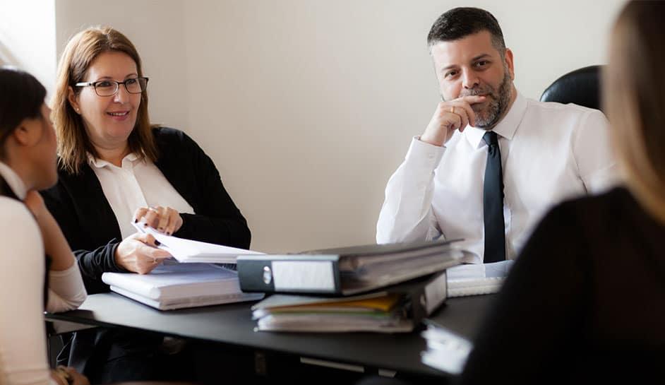 עורך דין כפיר דיין יושב ליד השולחן עם צוות המשרד