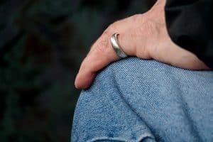 אדם עם טבעת כסף מניח יד על הרגל